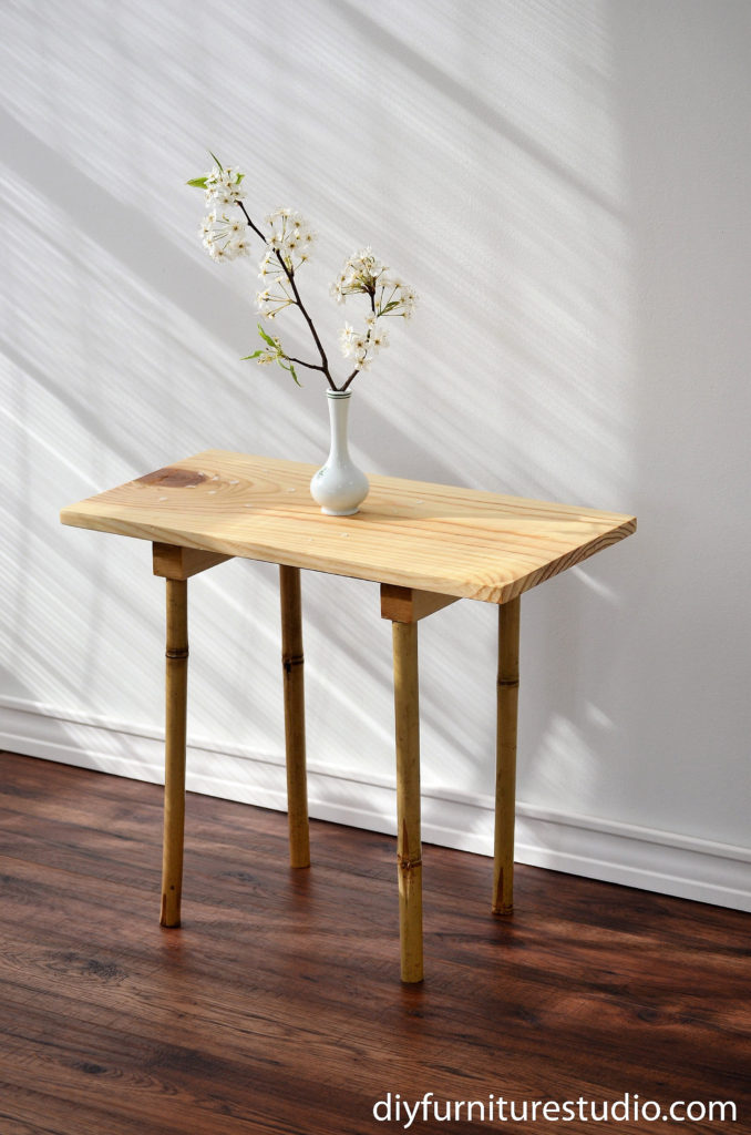 DIY side table made with upcycled bamboo garden stake legs.  I paired the bamboo legs with a simple pine board table top.