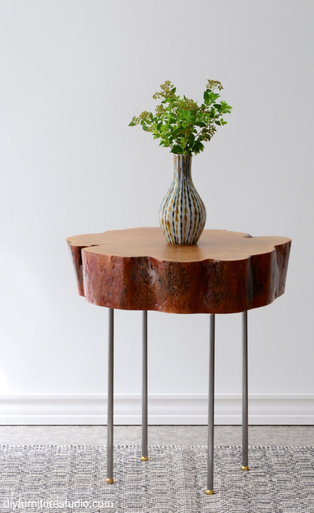 DIY Live edge tree slice side table with standalone legs made of lamp pipe, brass flanges, and brass ball feet.