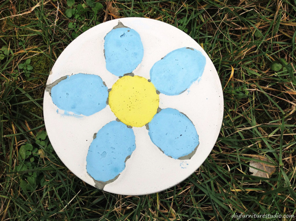 DIY Cement Stepping Stones with Embedded Colored Cement Designs.